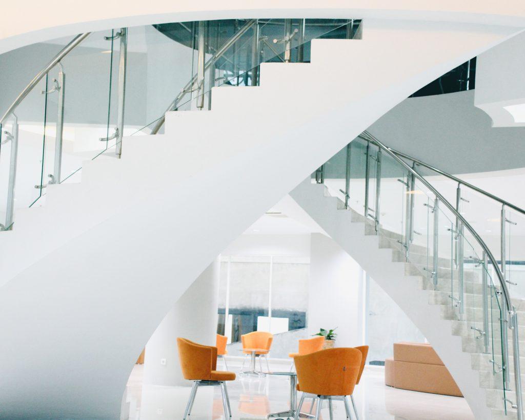 Farbiger Akzent durch Stühle in minimalistisch gehaltendem Atrium